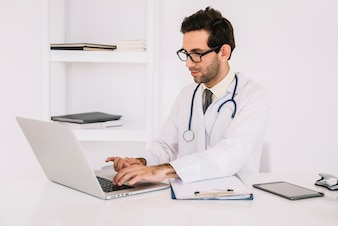 Young male doctor wearing eyeglasses using laptop in clinic