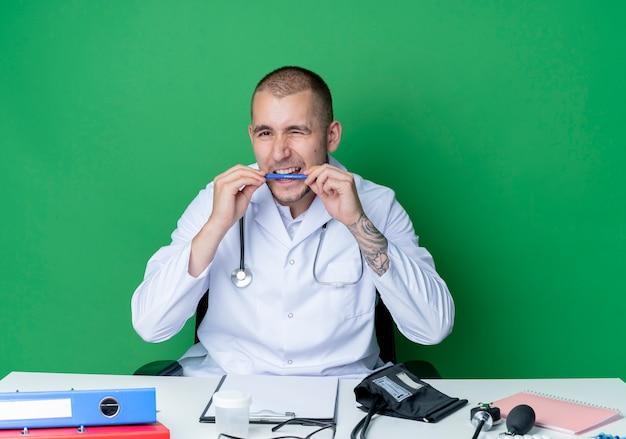 펜을 물고 녹색 배경에 고립 된 카메라에 윙크하는 작업 도구와 책상에 앉아 의료 가운과 청진기를 착용하는 젊은 남성 의사