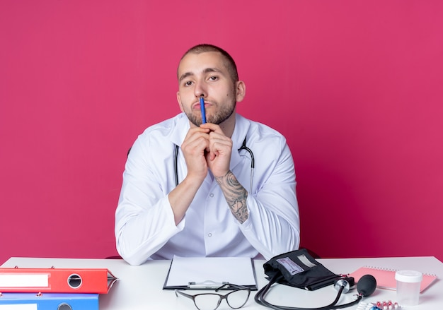 의료 가운과 청진기를 착용하고 작업 도구 펜을 들고 그것으로 입술을 만지고 분홍색 배경에 고립 된 카메라를보고 책상에 앉아 젊은 남성 의사