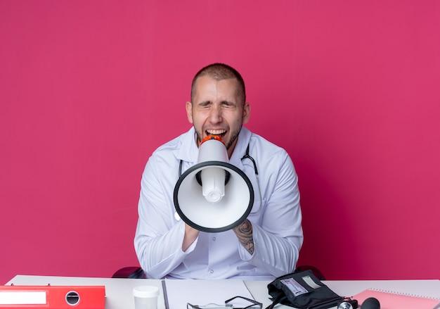 분홍색 배경에 고립 된 닫힌 눈 시끄러운 스피커에서 외치는 작업 도구와 책상에 앉아 의료 가운과 청진기를 착용하는 젊은 남성 의사