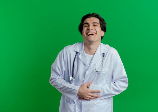Giovane medico maschio che indossa veste medica e stetoscopio che tiene la pancia e che ride con gli occhi chiusi isolati sulla parete con lo spazio della copia