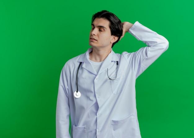 Giovane medico maschio che indossa veste medica e stetoscopio tenendo la mano dietro la testa con gli occhi chiusi isolati