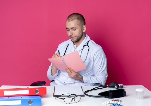 Young male doctor wearing medical robe and stethoscope sitting at desk with work tools holding and looking at note pad and writing something on it with pen isolated on pink background