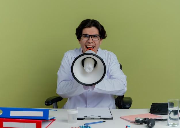 Giovane maschio medico indossa abito medico e stetoscopio con gli occhiali seduto alla scrivania con strumenti medici cercando di parlare da altoparlante isolato