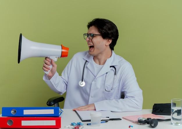 Giovane medico maschio che indossa veste medica e stetoscopio con gli occhiali seduto alla scrivania con strumenti medici girando la testa a lato gridando in altoparlante isolato sulla parete verde oliva