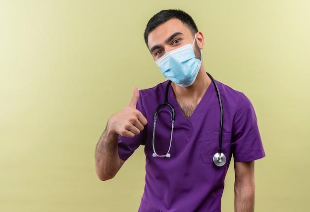 Молодой мужчина-врач в фиолетовой одежде хирурга и в медицинской маске со стетоскопом его большой палец вверх на изолированной зеленой стене