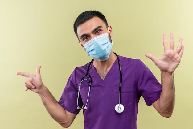 孤立した緑の壁にさまざまなジェスチャーを示す紫色の外科医の服と聴診器の医療マスクを身に着けている若い男性医師