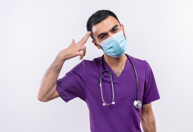 Молодой мужчина-врач в фиолетовой одежде хирурга и в медицинской маске со стетоскопом показывает жест пистолета на изолированной белой стене