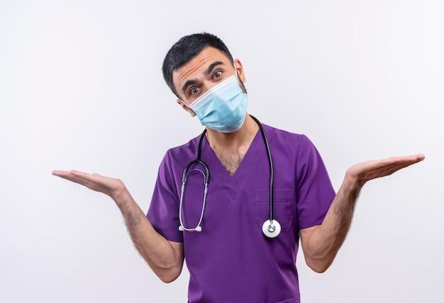 Молодой мужчина-врач в фиолетовой одежде хирурга и в медицинской маске со стетоскопом раскладывает руки на изолированной белой стене