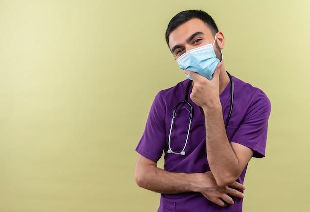 Giovane medico maschio che indossa abiti chirurgo viola e maschera medica stetoscopio mise la mano sul mento sul muro verde isolato