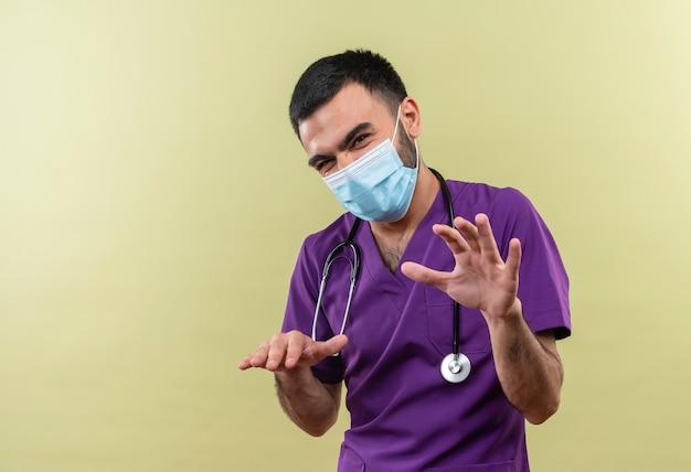 Giovane medico maschio che indossa abbigliamento chirurgo viola e maschera medica stetoscopio che mostra dimensioni diverse sulla parete verde isolata
