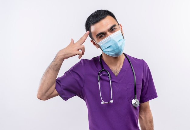 Young male doctor wearing purple surgeon clothing and stethoscope medical mask showing pistol gesture on isolated white wall