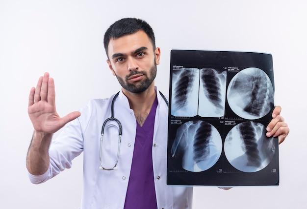 孤立した白い壁に停止ジェスチャーを示すx線を保持している聴診器の医療用ガウンを身に着けている若い男性医師