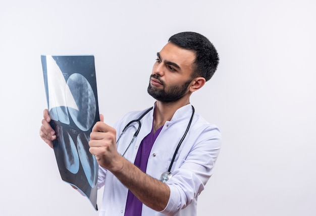 Молодой мужчина-врач в медицинском халате со стетоскопом смотрит на рентгеновский снимок в руке на изолированном белом