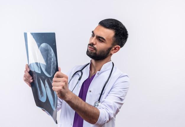 Giovane medico maschio che indossa l'abito medico dello stetoscopio che esamina i raggi x nella sua mano su bianco isolato