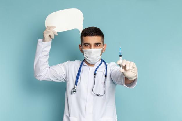 Giovane medico maschio in vestito bianco con lo stetoscopio blu che tiene l'iniezione e il lavoro bianco della segnaletica