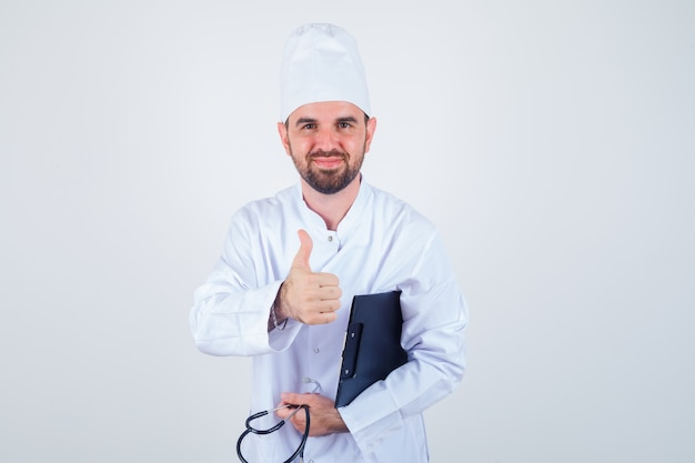Young male doctor in white uniform holding clipboard, stethoscope, offering handshake as greeting and looking gentle , front view.