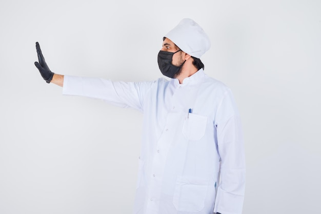 Young male doctor in white uniform showing stop gesture and looking confident , front view.