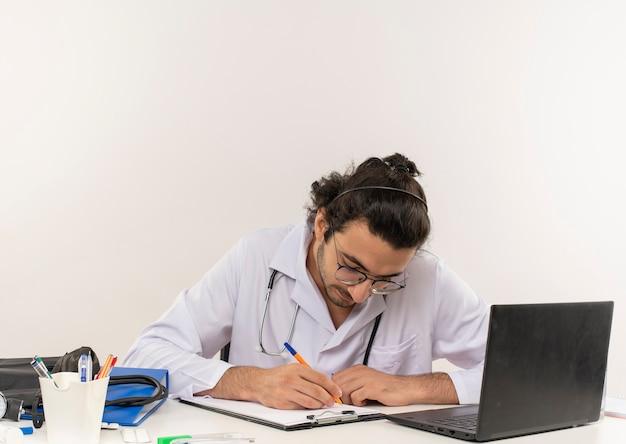 Giovane medico maschio con occhiali medicali indossando abito medico con seduta stetoscopio