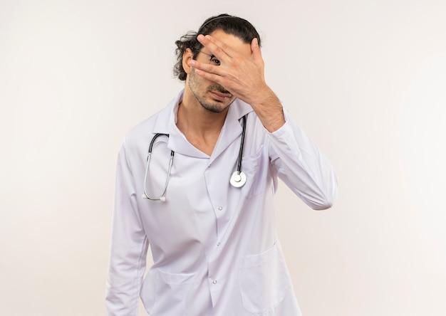 청진기로 흰 가운을 입은 광학 안경을 가진 젊은 남성 의사가 눈을 덮었습니다.