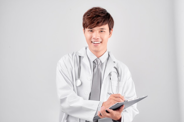 Young male doctor with stethoscope in uniform and make notes isolated on white background
