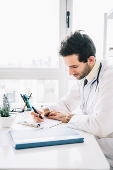 Young male doctor writing on clipboard in clinic