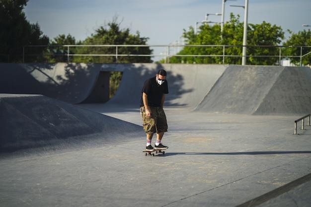 Молодой мужчина делает разные трюки со скейтбордом в парке в медицинской маске