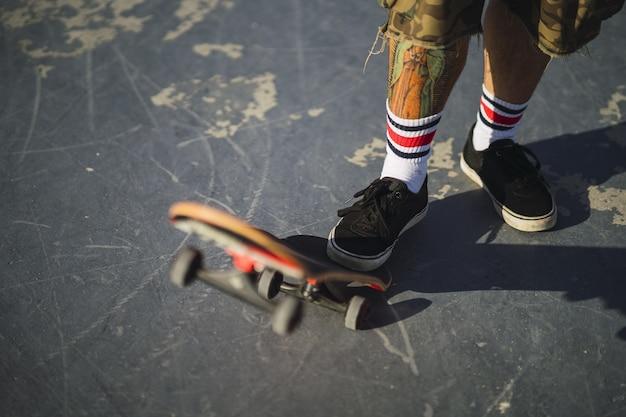 Молодой мужчина делает разные трюки со скейтбордом в парке