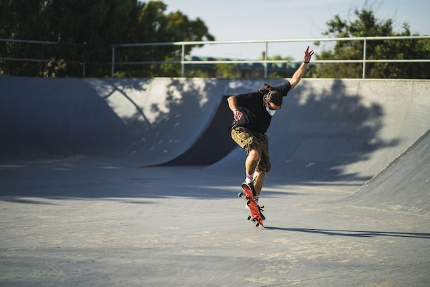 Young male doing different tricks with a skateboard in the park wearing a medical face mask