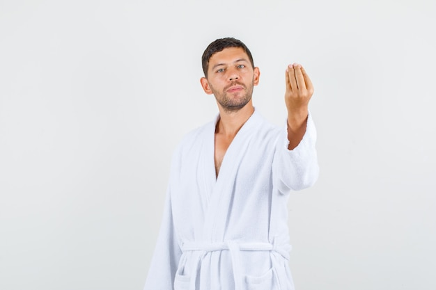 Young male doing italian gesture and smiling in white bathrobe , front view.