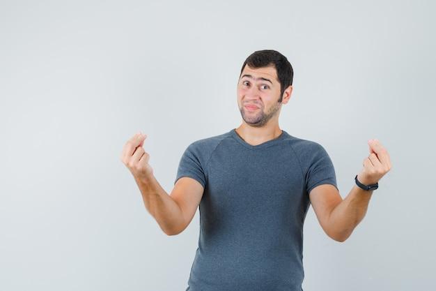 Молодой мужчина делает денежный жест в серой футболке