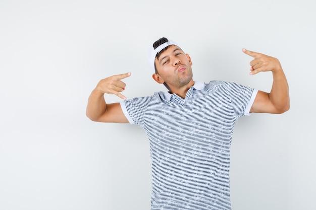 Giovane maschio che fa il simbolo del rock in t-shirt e berretto e sembra fresco