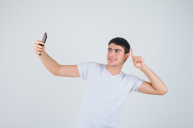 Young male doing selfie while pointing up in t-shirt and looking cheery , front view.