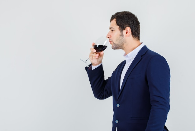 Young male drinking alcohol in dark blue suit and looking peaceful .