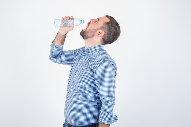 Young male drinking from plastic water bottle in shirt, jeans and looking delighted , front view.
