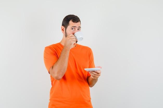 주황색 티셔츠를 입고 차를 마시고 조심스럽게 앞을 바라보는 젊은 남성.
