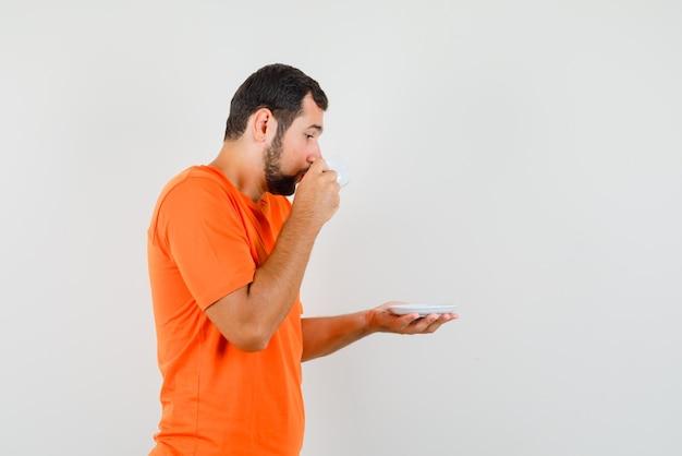 오렌지 티셔츠를 입고 차를 마시고 조심스럽게 바라보는 젊은 남성.