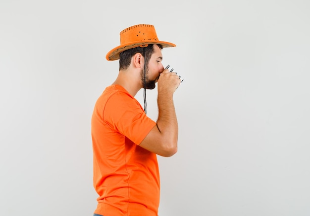 주황색 티셔츠, 모자를 쓰고 귀엽게 생긴 젊은 남성이 차를 마시고 있습니다. .