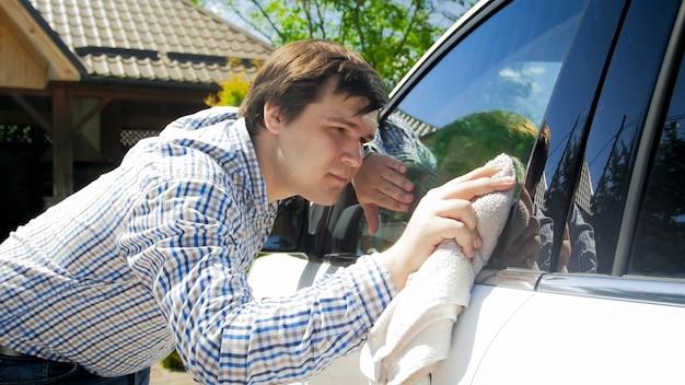 Молодой водитель мужского пола чистит и моет окна своего автомобиля.
