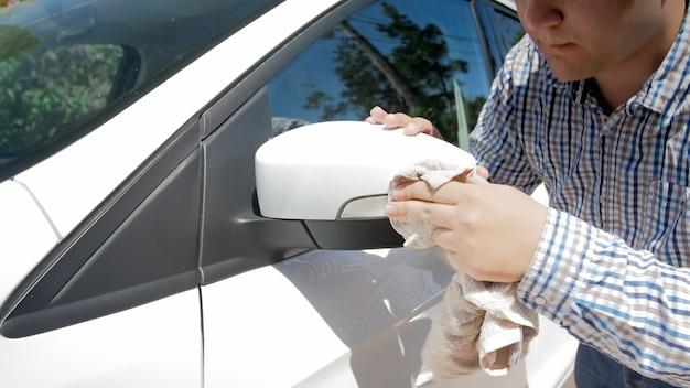 Молодой водитель мужского пола, чистящий окна заднего вида своего автомобиля.