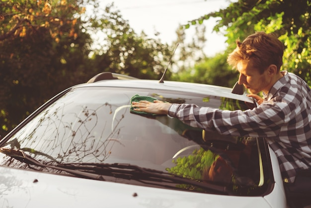 Young male driver wipe his car outdoor on a summer days