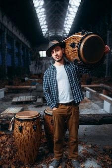 Young male drummer holds wooden drum on the shoulder, factory shop. djembe, musical percussion instrument,