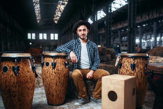 若い男性ドラマーはアフリカの木製ドラムに対してポーズします。