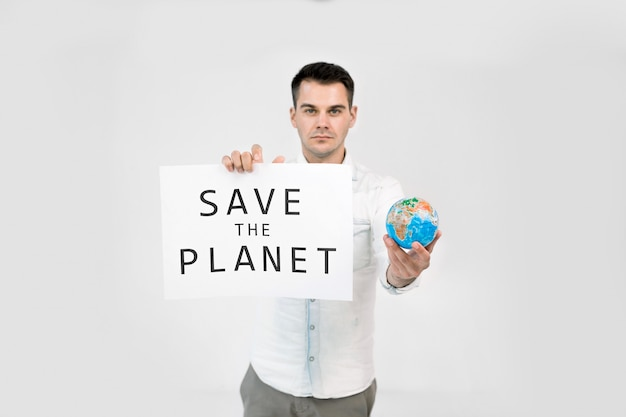 Young male ecologist holding paper placard with save the earth text