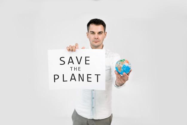 Молодой мужчина-эколог держит бумажный плакат с текстом «спасите землю»