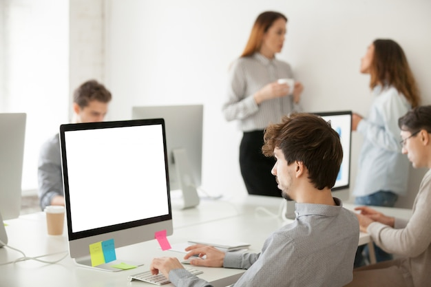 Young male employee working on computer writing email in office