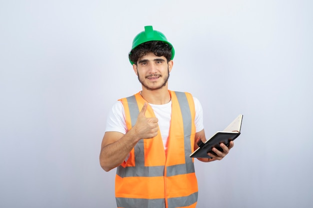 Young male engineer in green hardhat holding notebook on white background. high quality photo