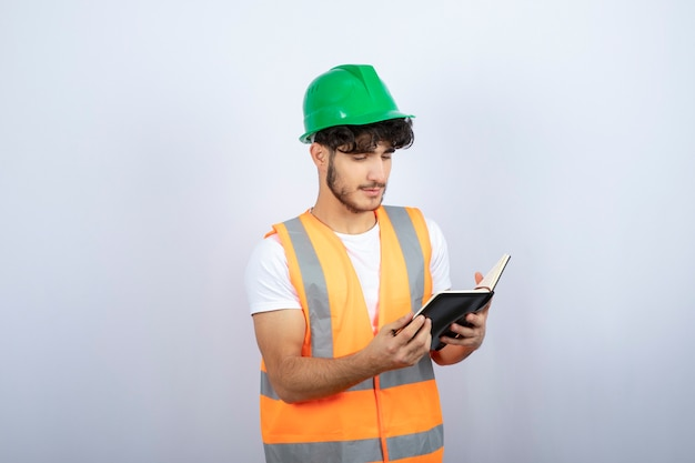 Young male engineer in green hardhat reading notes on white background. high quality photo