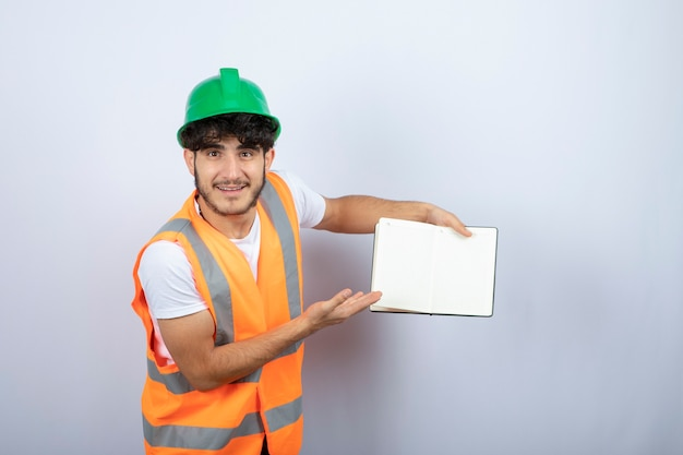 Young male engineer in green hardhat showing notes on white background. high quality photo