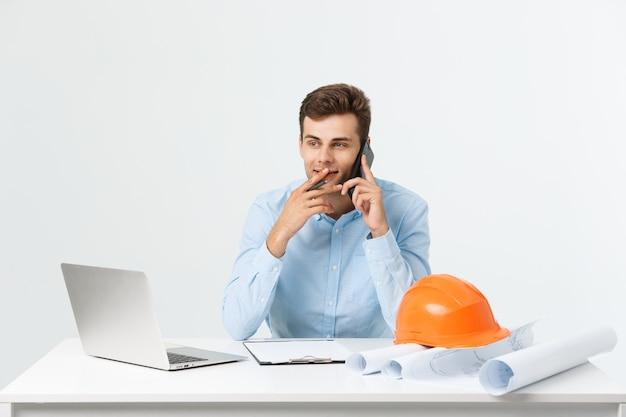 Giovane ingegnere maschio che parla al telefono nel suo ufficio su grigio.